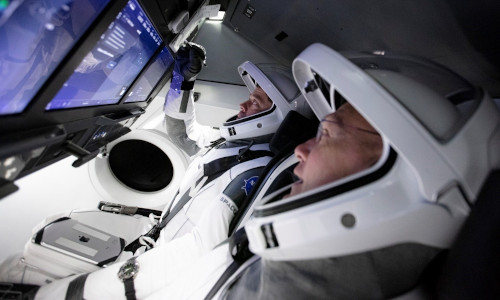 Astronauts at the controls of a space capsule.